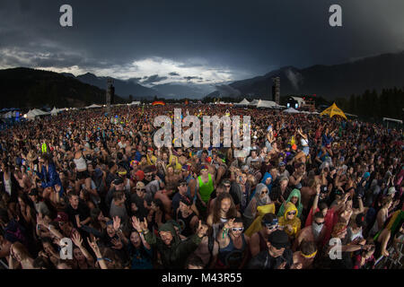 Thousands of people celebrating at a music festival in a field with the sun setting in the mountains in the background. - Stock Photo