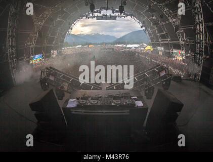 Turntables set up on stage with thousands of people waiting and the sun is setting in the background behind the - Stock Photo