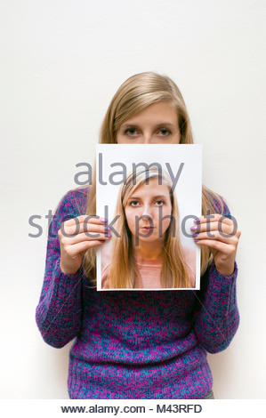 young woman hiding her face behind a photo portrait of herself - Stock Photo