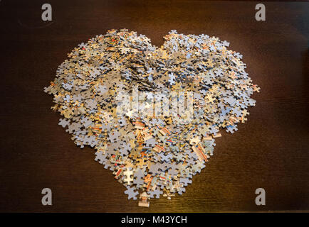 Jigsaw puzzle pieces piled on a dark wood table in the shape of a heart. - Stock Photo