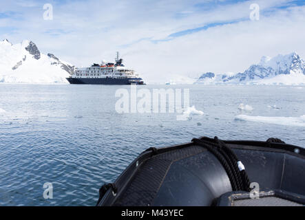 A ship anchored in Paradise Bay Antarctica, photographed from a Zodiak boat. Snow covered mountains surround the - Stock Photo