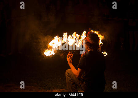 Young male performing fire juggling in front of excited crowd. Fire show and performance at night. - Stock Photo