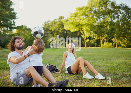 Family playing with a ball in the park.  - Stock Photo