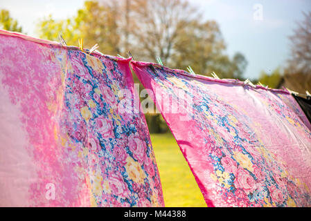 Holidays and vacation on countryside at camping. Just washed, fresh and aromatic cotton bed sheets and linen, hang - Stock Photo
