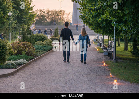 Happy couple holding hands and walking in park on lit candle path during sunset. Romantic summer evening, love is - Stock Photo