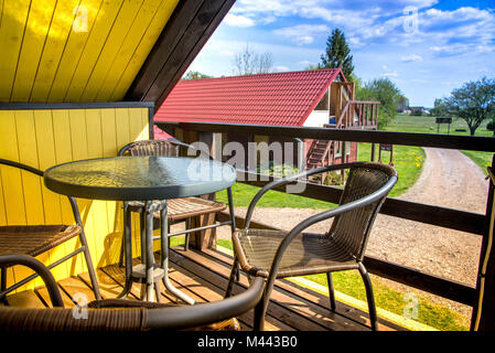 Chilling and relaxing in vacation at guest house in countryside. A scene of balcony, coffee table and chairs, while - Stock Photo