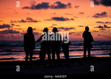 Golden, colorful, abstract sea sunset view at horizon with people silhouettes Vibrant sky landscape and waves in - Stock Photo