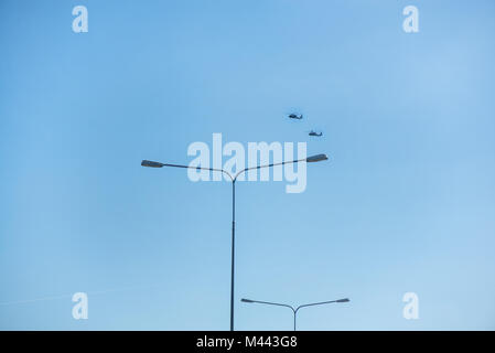 Military helicopters flying in the sky over a city and crowded event, taking photos, filming from above on clear - Stock Photo