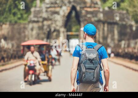 Tourist in the ancient city. Young man with backpack coming to ancient monuments. Siem Reap, Cambodia - Stock Photo