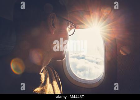 Young man looking out through window of the airplane during beautiful sunrise. - Stock Photo