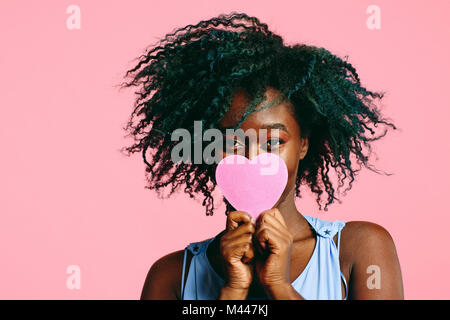 Girl with blueish black curly hair holding a pink heart in front of her face - Stock Photo