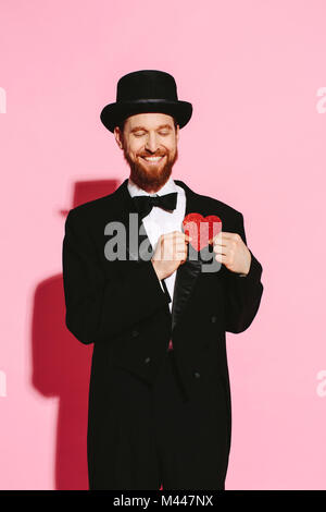 Smiling man with closed eyes in suit and top hat holding red heart on his chest - Stock Photo