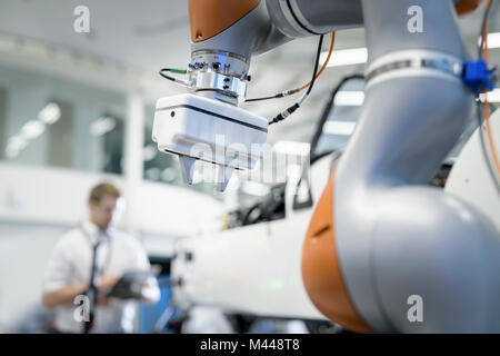 Engineer and robot inspecting car in robotics research facility - Stock Photo