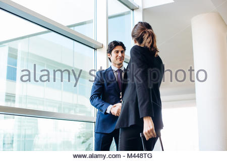 Businessman and businesswoman with wheeled luggage in hotel building - Stock Photo