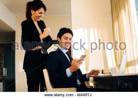 Businessman and businesswoman sharing text message in hotel room - Stock Photo