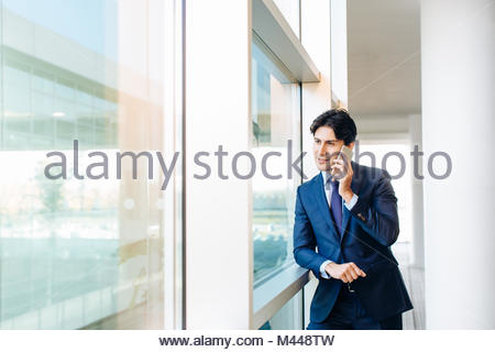 Businessman using mobile phone by window - Stock Photo