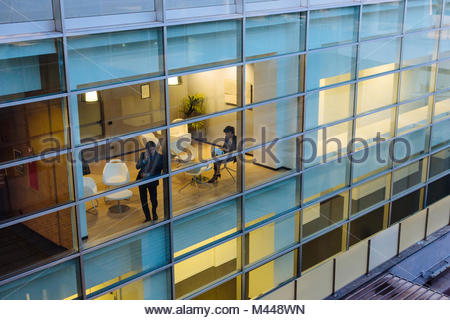 Businessman and businesswoman having discussion by window - Stock Photo