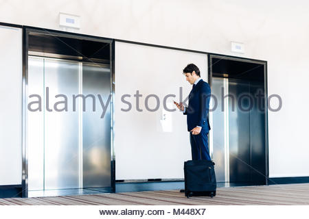 Businessman with wheeled luggage by hotel lift - Stock Photo