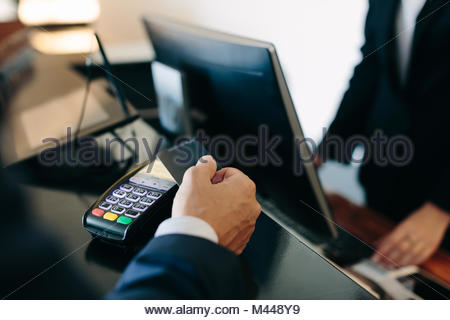 Businessman making contactless payment at hotel reception - Stock Photo