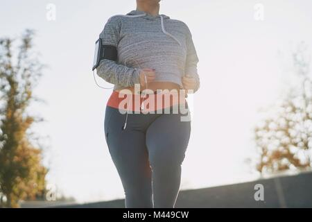Curvaceous young female runner running in park, mid section - Stock Photo