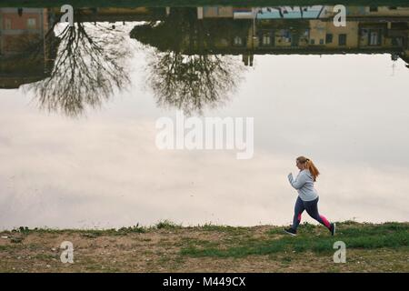 Curvaceous young female runner running on riverside - Stock Photo