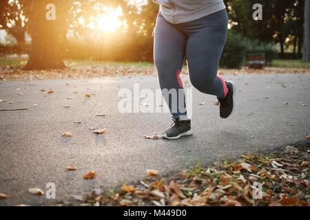Curvaceous young female runner running in park, waist down - Stock Photo