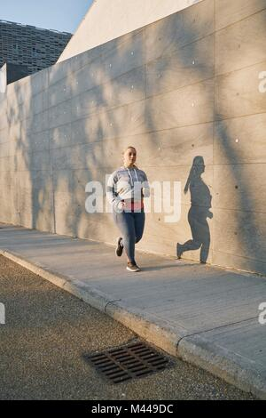 Curvaceous young female runner running along sidewalk - Stock Photo