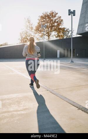 Curvaceous young female runner running, rear view - Stock Photo