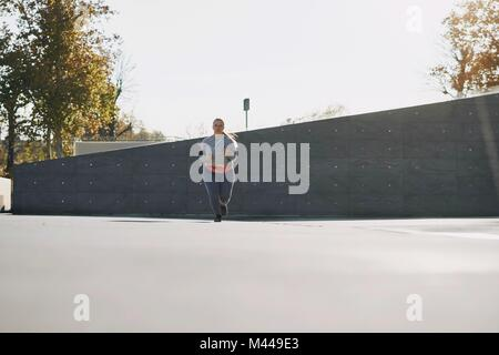 Curvaceous young female runner running in urban setting - Stock Photo
