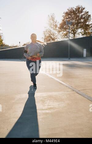 Curvaceous young female runner running in sunlight - Stock Photo