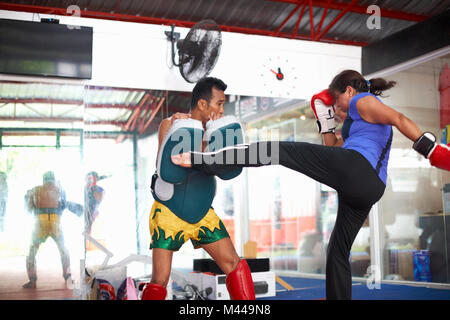 Mature woman practicing kickboxing with male trainer in gym - Stock Photo