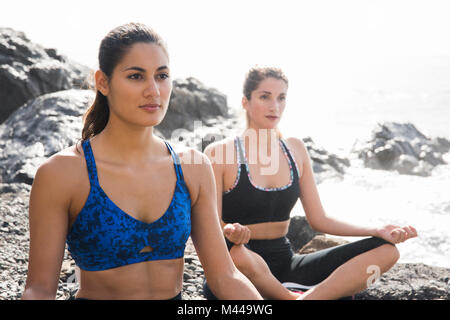 Two young women practicing yoga lotus pose on beach, Las Palmas, Canary Islands, Spain - Stock Photo