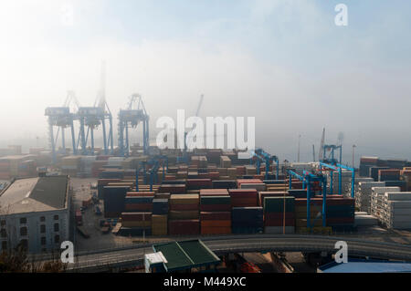 Shipping containers and harbour cranes in mist, Valparaiso, Chile - Stock Photo