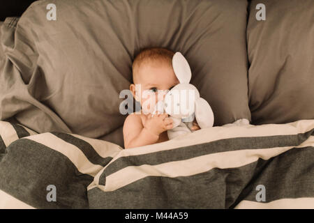 Portrait of baby girl lying in bed hugging toy rabbit, overhead view - Stock Photo