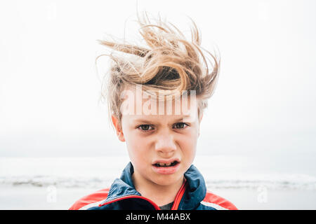 Portrait of boy on beach, messy hair, making face, close-up - Stock Photo