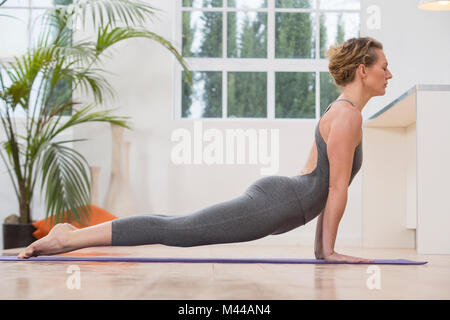 Woman at home, doing yoga, in yoga position - Stock Photo