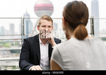 Over shoulder view of young businessman and woman having meeting at sidewalk cafe in Shanghai financial centre, - Stock Photo