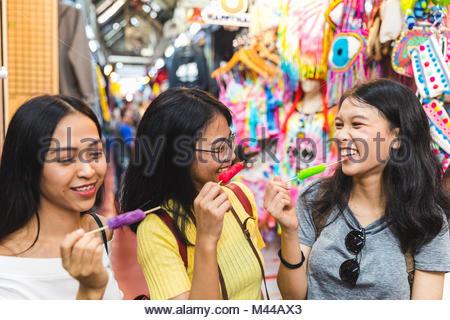 Happy young women with ice lollies in bazaar, Bangkok, Thailand - Stock Photo