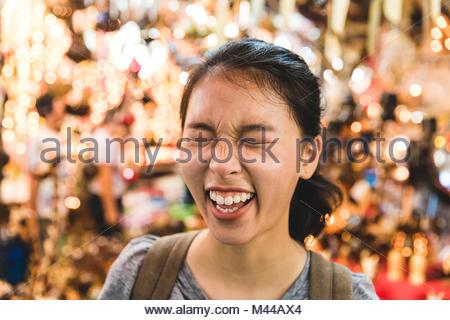 Tourist laughing in bazaar, Bangkok, Thailand - Stock Photo