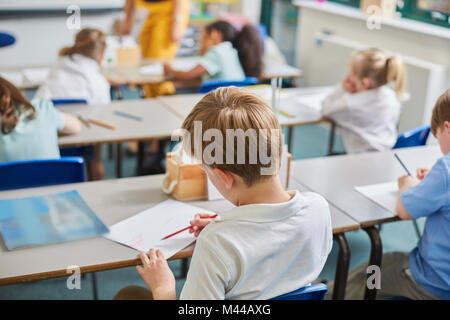 Primary schoolboy and girls doing schoolwork at classroom desks, rear view - Stock Photo