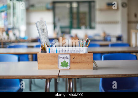 Classroom desk with wooden box full of pencils and rulers in primary school classroom - Stock Photo