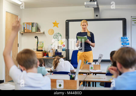 Schoolboy with hand raised in classroom lesson at primary school - Stock Photo