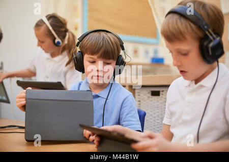Schoolboys and girl listening to headphones in class at primary school - Stock Photo