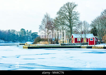 Red wooden cabin in coastal winter environment. Snow cover the ground and the bay is frozen. Island visible in background. - Stock Photo