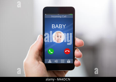 Hand Holding Smart Phone With Baby's Incoming Call On Display - Stock Photo