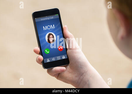 Close-up Of A Hand Holding Smart Phone With Mom's Incoming Call On Display - Stock Photo