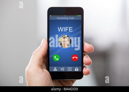 Close-up Of A Hand Holding Smart Phone With Wife's Incoming Call On Display - Stock Photo
