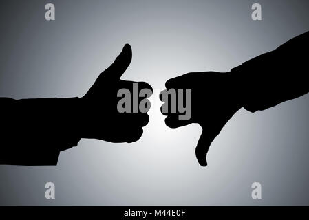 Silhouette Of Two Person's Hand Showing Thumb Up And Thumb Down Against Gray Background - Stock Photo
