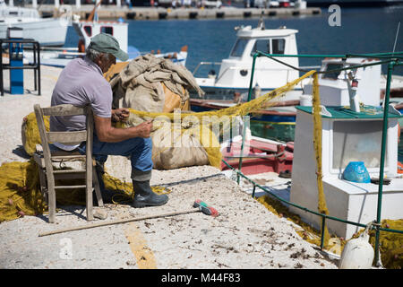 Fisherman repairing fishing nets on quayside, Kamares, Sifnos, Cyclades, Aegean Sea, Greek Islands, Greece, Europe - Stock Photo