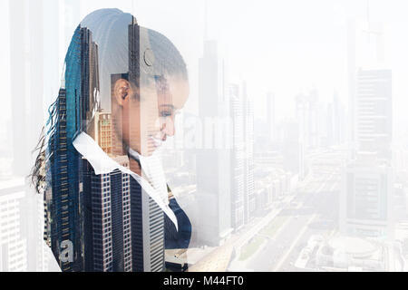 Digital composite image of young businesswoman smiling over city background - Stock Photo